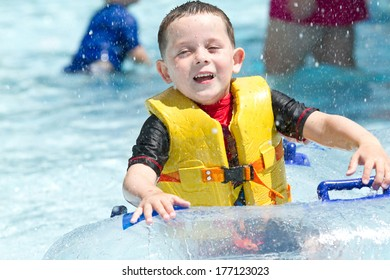 boy in swimming pool smiling, wearing a life vest