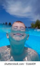 Boy swimming underwater in swimming pool