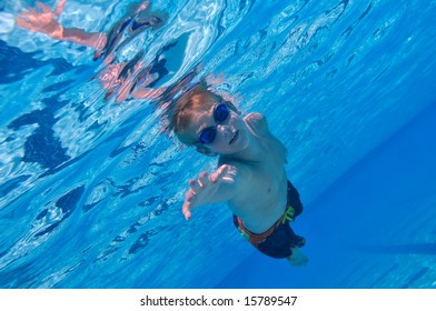 Boy swimming underwater, sunny outdoor conditions