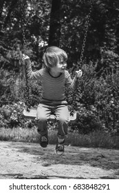 Boy swinging on the playground. Black and white, vintage look.