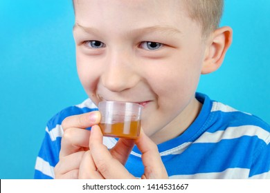 boy takes multi vitamin syrup on blue background, closeup