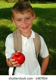boy taking an apple for his teacher on the first day of school