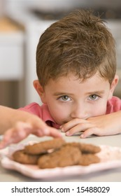 Boy taking biscuit from plate