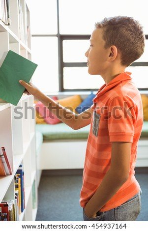 Boy Taking A Book From Bookshelf In Library At School