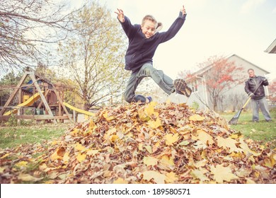 Boy taking a break from chores to jump in the leaves