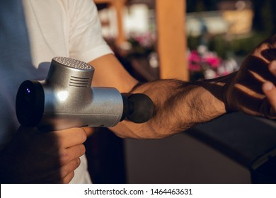 Boy taking gray and black machine to massage his arm and body at sunset at home in Dolomites, Italy