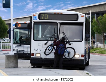 Boy taking his bike off the front of a bus