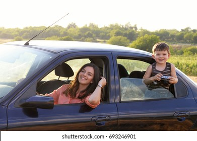 Boy taking photo of his mom on start of journey. Travel concept. Happy family in the car