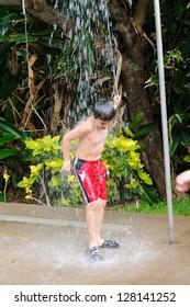 Boy taking shower outside