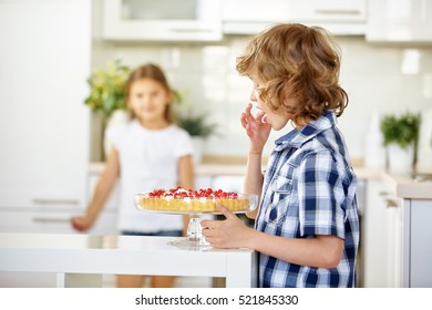 Boy tasting from fresh fruit cake with red currants in the kitchen