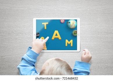 The boy teaches letters and numbers through playing games on the tablet.