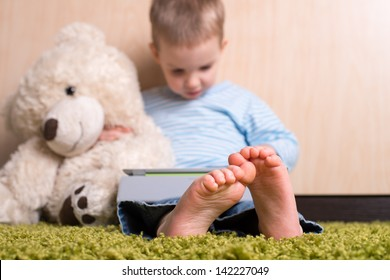 Boy and teddy bear with tablet computer, bare feet in focus
