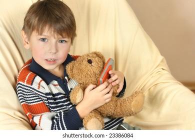 Boy with teddy bear talking at phone