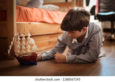 Boy teen plays with ship model on the floor in real children's room