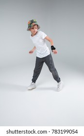 The boy teenager dancing widely with legs spread, slightly bent hands and with an emotional expression.