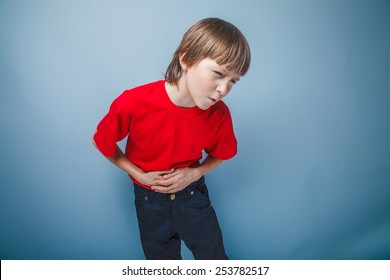 boy teenager European appearance in a red shirt holding his hand over his stomach on a gray background, pain