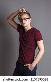 Boy teenager in glasses stands near wall in grey studio