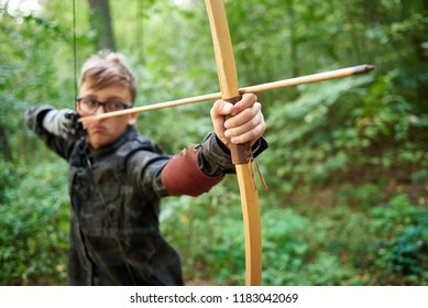 boy teenager has training, shoots a wooden bow in the forest