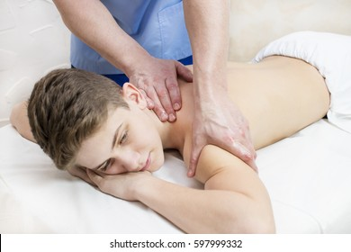 Boy teenager on the procedure of medical medical sports body massage