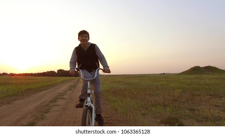 Boy teenager riding bicycle. Boy teenager riding bicycle goes to nature along the path steadicam shot motion video
