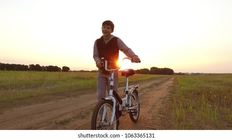 Boy teenager riding bicycle. the Boy teenager riding bicycle goes to nature along path steadicam shot motion video