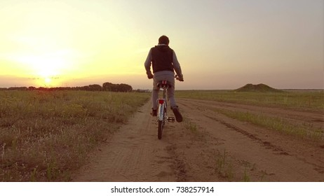 Boy teenager riding a bicycle. Boy teenager riding a bicycle goes to nature along the path steadicam shot video motion