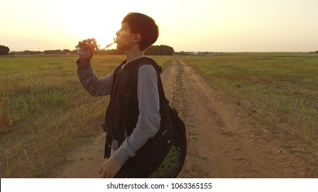 Boy teenager tourist drinking water from a plastic bottle in nature. Boy homeless vagabond drink water thirst