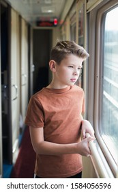 boy teenager trabeling by train, look at window