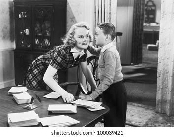 Boy telling secret to young woman