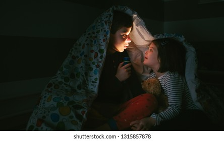 Boy telling a story of fear to his sister lighting up with a flashlight