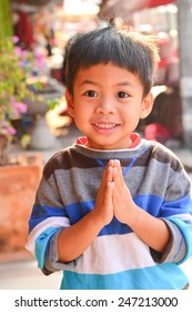 Boy in Thailand acting sawaddee mean Hello  in the Morning.