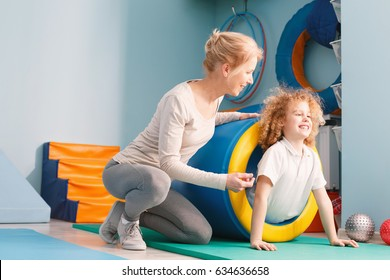 Boy in therapeutic tunnel, exercising with physiotherapist