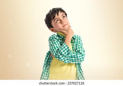 Boy thinking over ocher background