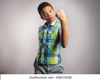 Boy threatening with his fist over grey background. Vertical Shot.