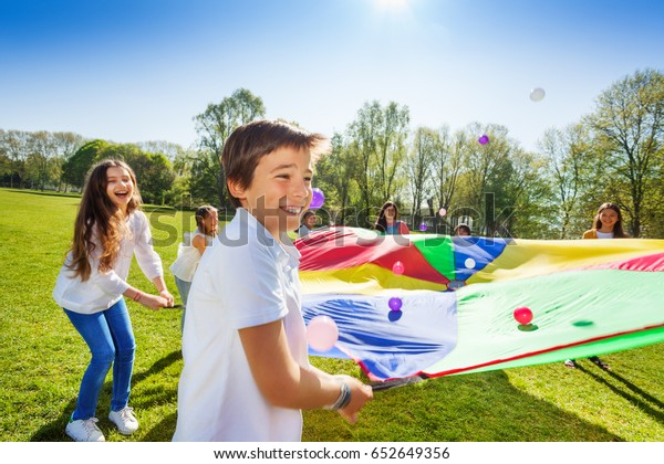 Boy throwing balls up by using rainbow parachute