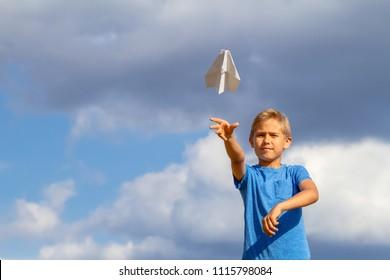 Boy throwing paper plane against blue sky