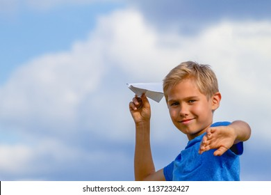 Boy throwing paper plane on summer day