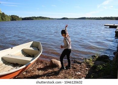 Boy throwing stones into lake