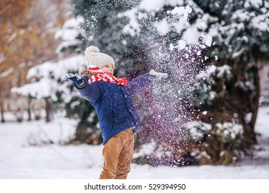 Boy throws snow and smiling happily