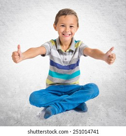Boy with thumb up over textured background