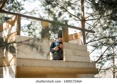 A boy is tighten the screw with a screwdriver building a tree house. Image with selective focus and toning