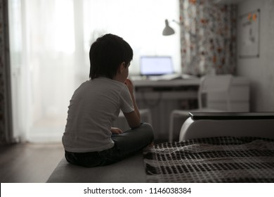 boy toddler sad on the couch in the real room at home, lifestyles