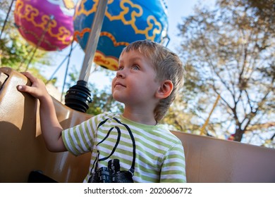 Boy toddler sits at a booth in the carrousel. Happy baby is at at amusement park . Smiling boy rides art attraction in a fairground. Leisure with family.