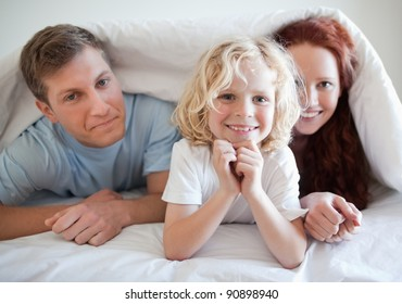 Boy together with his parents under bed cover