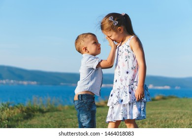 boy touching sister's nose on meadow at sea coastline