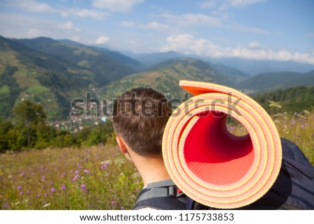 Boy with tourist equipment in the mountains