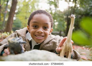 Boy with toy dinosaurs