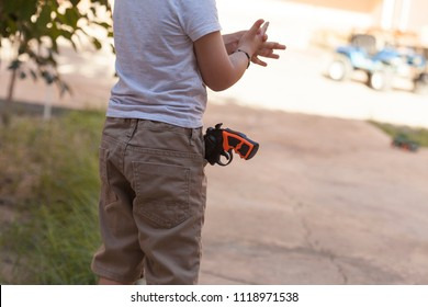 A boy with toy gun. Little boy with plastic gun in the jeans pocket. Happy boy with toy pistol gun playing at outdoors.