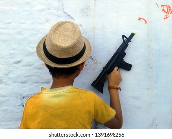 A boy with toy gun. Little boy with plastic gun in the jeans pocket. Happy boy with toy pistol gun playing at outdoors