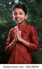 Boy with traditional Indian greeting 'Namaste' on an outdoor background